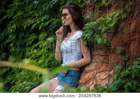 charming brunette with glasses posing in a park near the leaf and stone wall