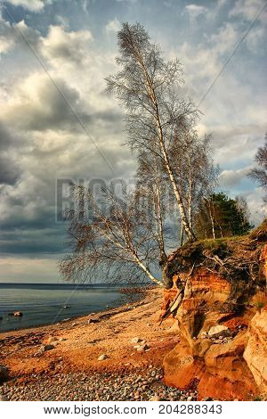 Rocks stones red cliff and waves on beach sand at the coast of sea water in summer evening sunset sky light