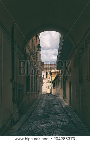 The narrow streets with tall buildings and tourist pointer to Dante in Rome on a summer day