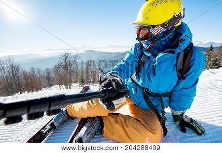 Close-up Shot Of A Skier Wearing Colorful Ski Gear Lying On The Snow On Top Of A Slope Taking A Self