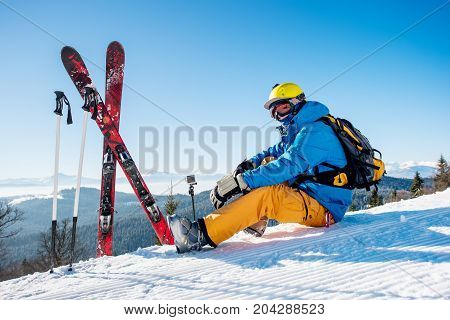 Shot Of A Professional Skier Sitting On Top Of The Mountain Near His Skiing Equipment Relaxing Enjoy