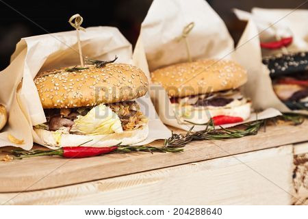 Fresh Hamburgers Wrapped In Paper On A Wooden Table