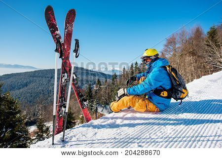 Professional Skier Sitting On Top Of The Mountain Near His Skiing Equipment Relaxing Enjoying Beauti