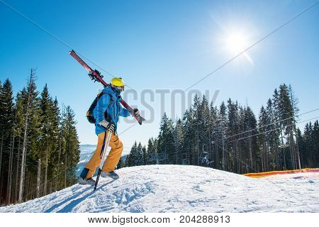 Shot Of A Male Skier Walking Up The Slope In The Mountains Carrying His Gear On His Shoulder On A Su