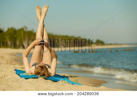 Summertime pleasures enjoying vacation concept. Woman in bikini sunbathing and relaxing on beach using smartphone checking social media and writing sms