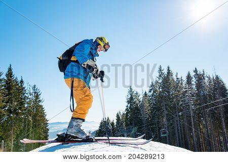 Low Angle Shot Of A Man Skiing In The Mountains, Wearing Skis, Enjoying Sunny Winter Day Outdoors Co