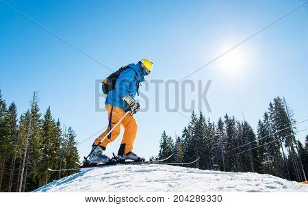 Low Angle Shot Of A Skier Getting Ready To Riding, Standing On Top Of The Hill In The Mountains At S