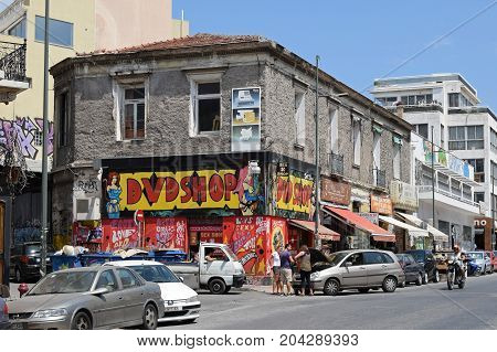 ATHENS GREECE - AUGUST 4 2016: Sex shop with pornographic movies on a rundown building and people in downtown Athens Greece.