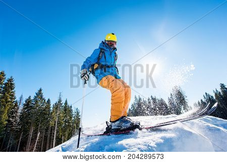 Rearview Shot Of A Skier Enjoying Skiing The Slope At Ski Resort In The Mountains On A Sunny Winter