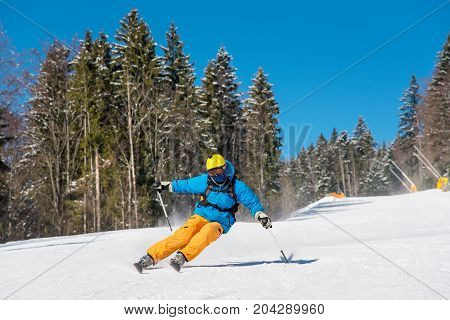 Freeride Skier Skiing In The Mountains At The Winter Resort. Blue Sky And Winter Forest On The Backg