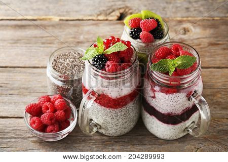 Chia Pudding With Berries In Glass Jars On Wooden Table
