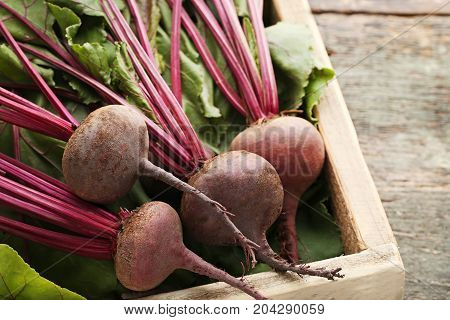 Fresh And Ripe Beets In Crate On Wooden Table