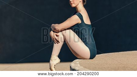 Ballet dancer sitting gracefully. Closeup of female ballet dancer sitting in pointe shoes resting her toes on the ground.