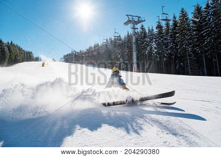 Skier Falling On The Slope On Fresh Powder Snow At Winter Resort. Blue Sky, Sun And Winter Forest On