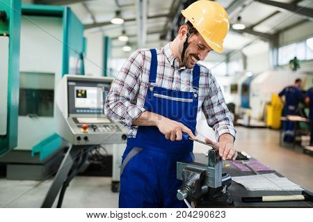 modern industrial machine operator working in metal industry factory