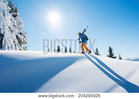 Low Angle Shot Of A Skier Walking On Top Of The Mountain With His Skis On His Shoulder On A Sunny Wi