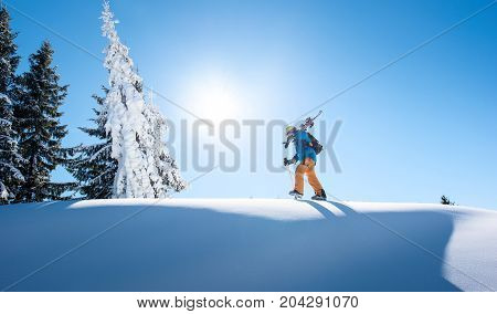 Male Skier Walking On Top Of The Mountain With His Skis On His Shoulder On A Sunny Winter Day Sunlig