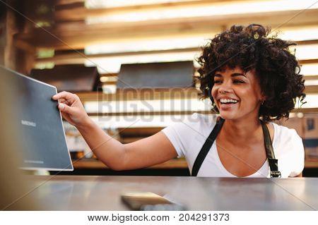 Woman Displaying Menu Card At The Counter