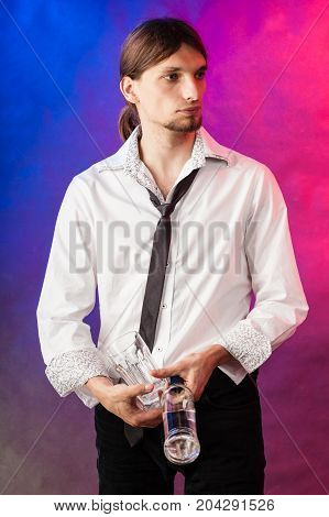 Alcohol liquor party relax flair bartending concept. Barman with bottle and glasses. Youthful tapster on colorful background.
