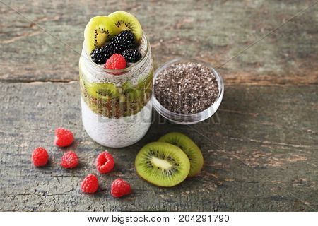 Chia Pudding With Berries In Bottle On Wooden Table