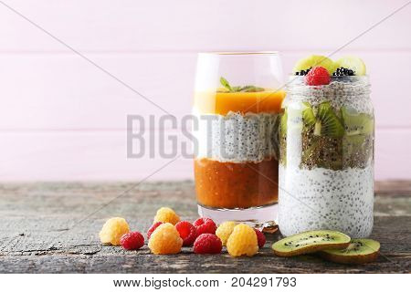 Chia Pudding With Berries In Glass On Wooden Table