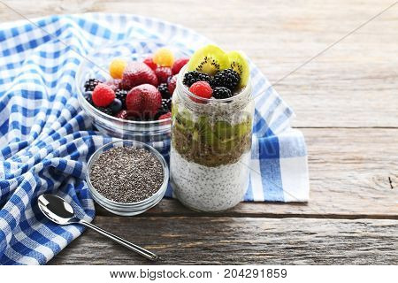 Chia Pudding With Berries In Glass On Grey Wooden Table
