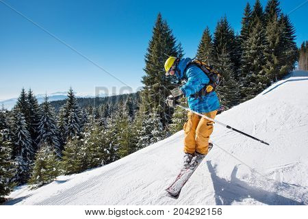 Shot Of A Skier Jumping In The Air While Riding Down The Slope In The Mountains On A Sunny Winter Da