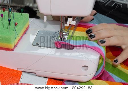 Woman's hands with dress at sewing machine. Tailoring Process - Women's hands behind her sewing