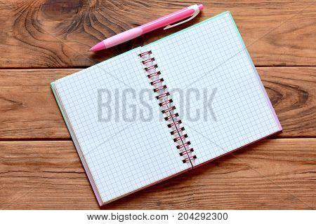 Blank open paper notebook for writing notes, pen on wooden table. Paper notebook worksheet with empty place for text. Closeup. Top view