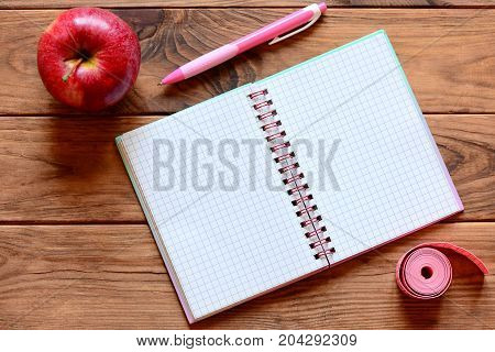 Paper notebook with blank pages, pen, apple, measuring tape in centimeters on a desk. Workout and dieting diary with empty place for text. Female slimming concept. Top view