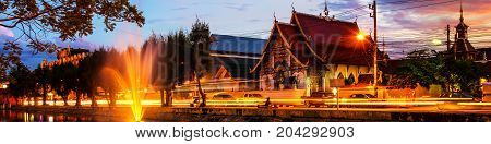 Chiang Mai Thailand at sunset. Lively street in popular touristic town Chiang Mai Thailand. With illuminated historical buildings and water reflection.