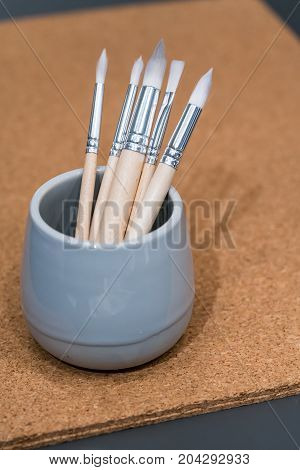 Variety of white paint brushes on cork board background with copy space