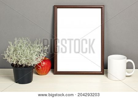 Brown frame mockup with plant pot mug and apple on wooden shelf. Empty frame mock up for presentation design. Template framing for modern art.