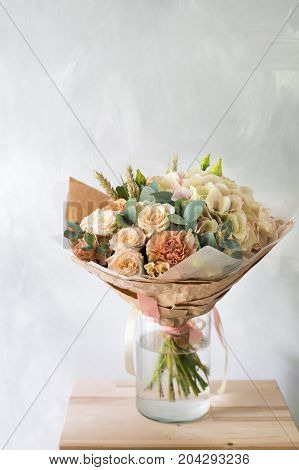 Close-up floral composition with roses and mix flowers on a gray background. caramel-cream gamma