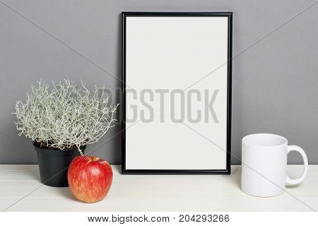 Black frame mockup with plant pot mug and apple on wooden shelf. Empty frame mock up for presentation design. Template framing for modern art.