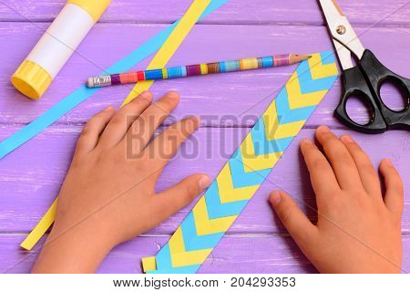 Child made a bookmark from yellow and blue folded paper. Child shows a paper colored bookmark. Stationery on a bright wooden table. Children workplace in school or at home