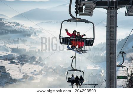 Couple Snowboarders Having Fun On A Ski Lift In Ski Resort With Beautiful Background Of Snow-covered