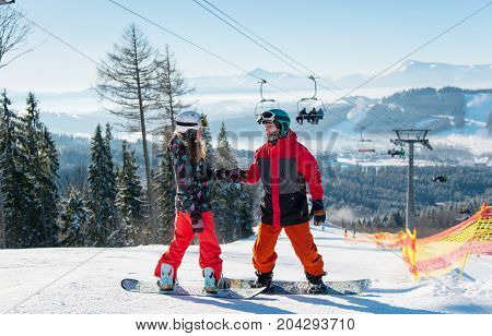 Pair Of Snowboarders On Top Of A Ski Slope At Winter Resort Downhill On A Sunny Day. Man Holds A Wom