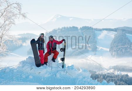 Pair Of Snowboarders On Top Of A Mountain With A Beautiful Scenery Of Snow-capped Mountains And Fore