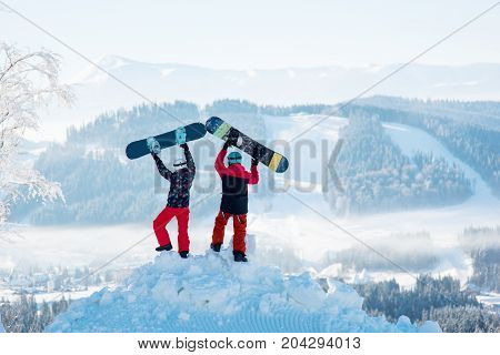 Two People Stand With Their Backs On A Snowdrift And Raise Their Snowboards Up Against A White Haze