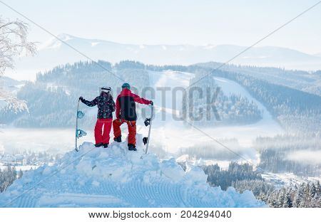 Two Snowboarders Enjoy The Snow-white Scenery Of Mountains And Forests Of The Carpathians From The H