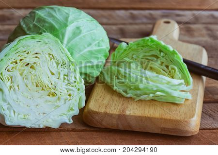 Chopped fresh cabbage on wood cutting board for food. Use knife kitchen cutting cabbage prepare for cooking. Cut or sliced fresh cabbage to shredded for coleslaw salad or other food. Sliced or chopped cabbage prepare for cooking.