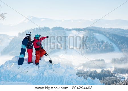 Couple Snowboarders Man And Woman Enjoying Beautiful Natural Landscape On Top Of The Hill On A Sunny