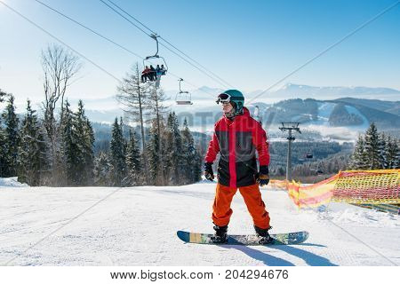 Man Standing On His Snowboard On A Ski Slope At Winter Resort With Ski Lifts Visible Behind On Backg