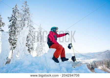 Man Snowboarder Sitting On Top Of A Snowy Hill With His Snowboard Enjoying Stunning Mountains View S
