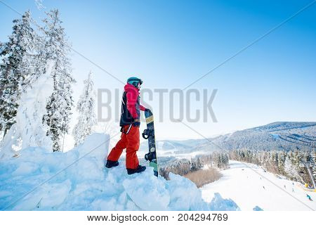 Full Length Shot Of A Male Snowboarder Standing On Top Of A Slope Looking Around Enjoying The View O