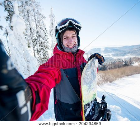 Shot Of A Happy Young Male Snowboarder Taking A Selfie. Standing On Top Of The Mountain At Ski Resor