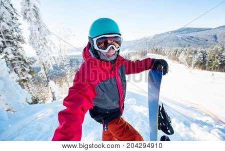 Shot Of A Man Snowboarder Taking A Selfie, Standing On The Slope Of The Hill At Ski Resort On A Beau