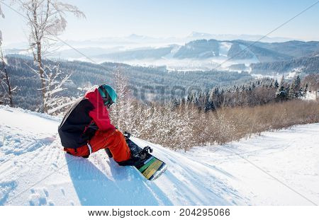 Shot Of A Male Snowboarder In Winter Sportswear Helmet And Skiing Mask Sitting On The Slope Preparin