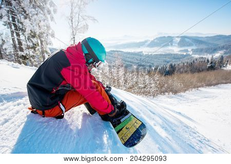 Man Snowboarder Sitting And Preparing For Riding The Slope At Ski Resort In The Mountains Copyspace